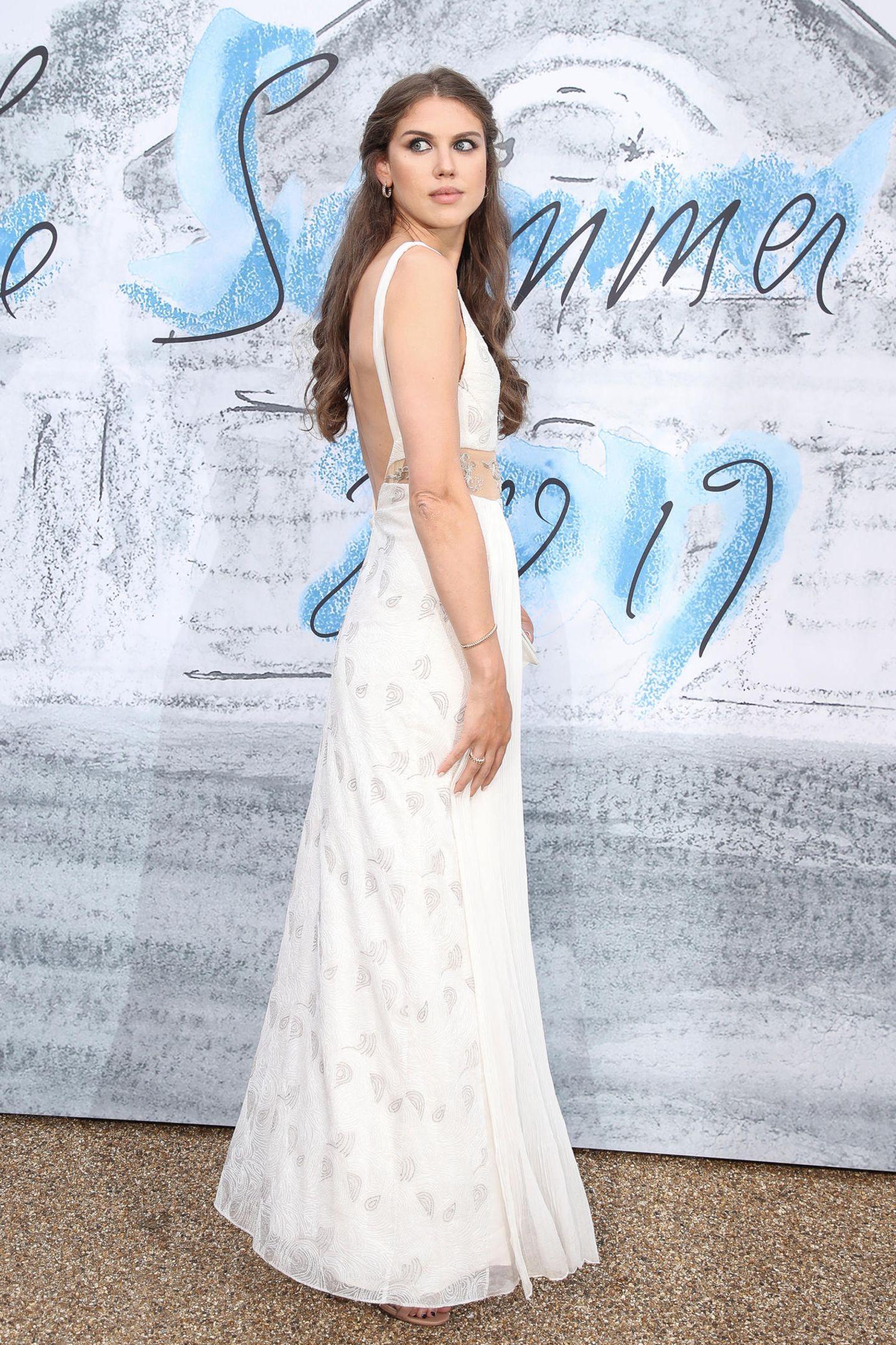 Lady Sabrina Percy wirkt in einem weißen Kleid ganz elfenhaft. Es bezaubert durch einen tiefen Rückenausschnitt, einen transparenten Einsatz in der Taille und feinstem 3D-Stoff.
