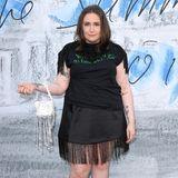 """Lena Dunham versucht sich daran, ein Statement-Shirt auf die 20er-Jahre zu trimmen. Mit Fransen am Rock sowie an den Schulterteilen versucht sie den Flair der Zeit wieder aufleben zu lassen. Doch wie genau soll man den Aufdruck ihres Oberteils verstehen? """"Würdest du mit mir ins Bett gehen?"""", steht darauf. Wir sind verwirrt."""