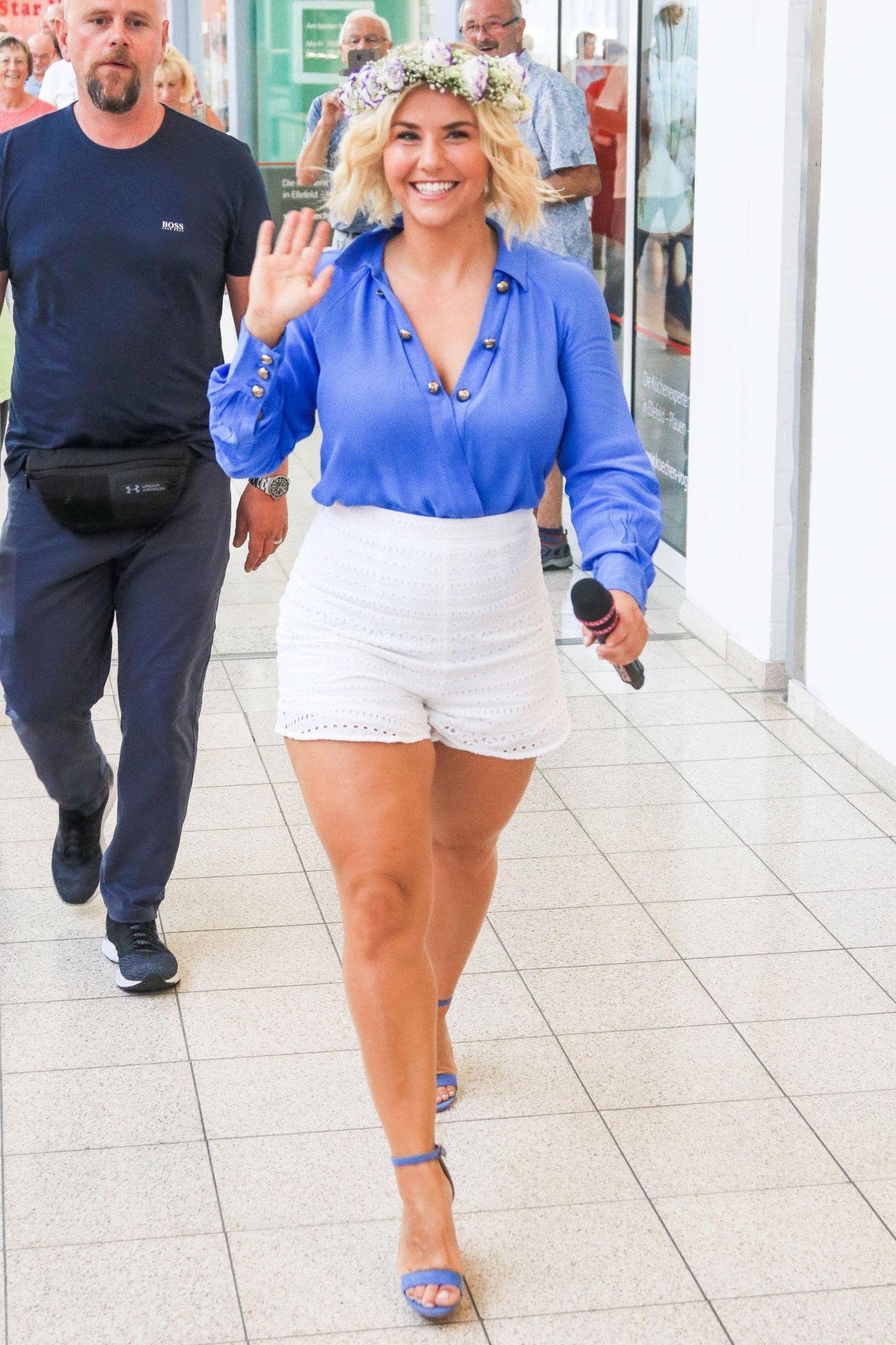 Mit einem strahlenden Lächeln trifft Schlagerstar Beatrice Egli bei einer Autogrammstunde ein. Die Blondine trägt eine weiße, kurze High-Waist-Shorts in Kombination mit einer knalligen, blauen Bluse und farblich abgestimmten Sandalen. Ein Look, der ihre Kurven perfekt in Szene setzt ...