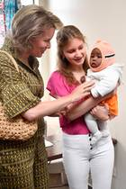 Dort verlieben sich die belgische Königin und ihre Tochter auf der Stelle in einBaby. Prinzessin Elisabeth nimmt das kleine Kind vorsichtig hoch.