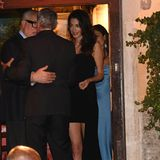 """In einem schwarzen Kleid des Labels """"Cinq à Sept"""" zeigt sich Amal Clooney von ihrer eleganten Seite. Dazu trägt sie ihr dunkles Haar offen, rote Lippen und silberne Creolen."""