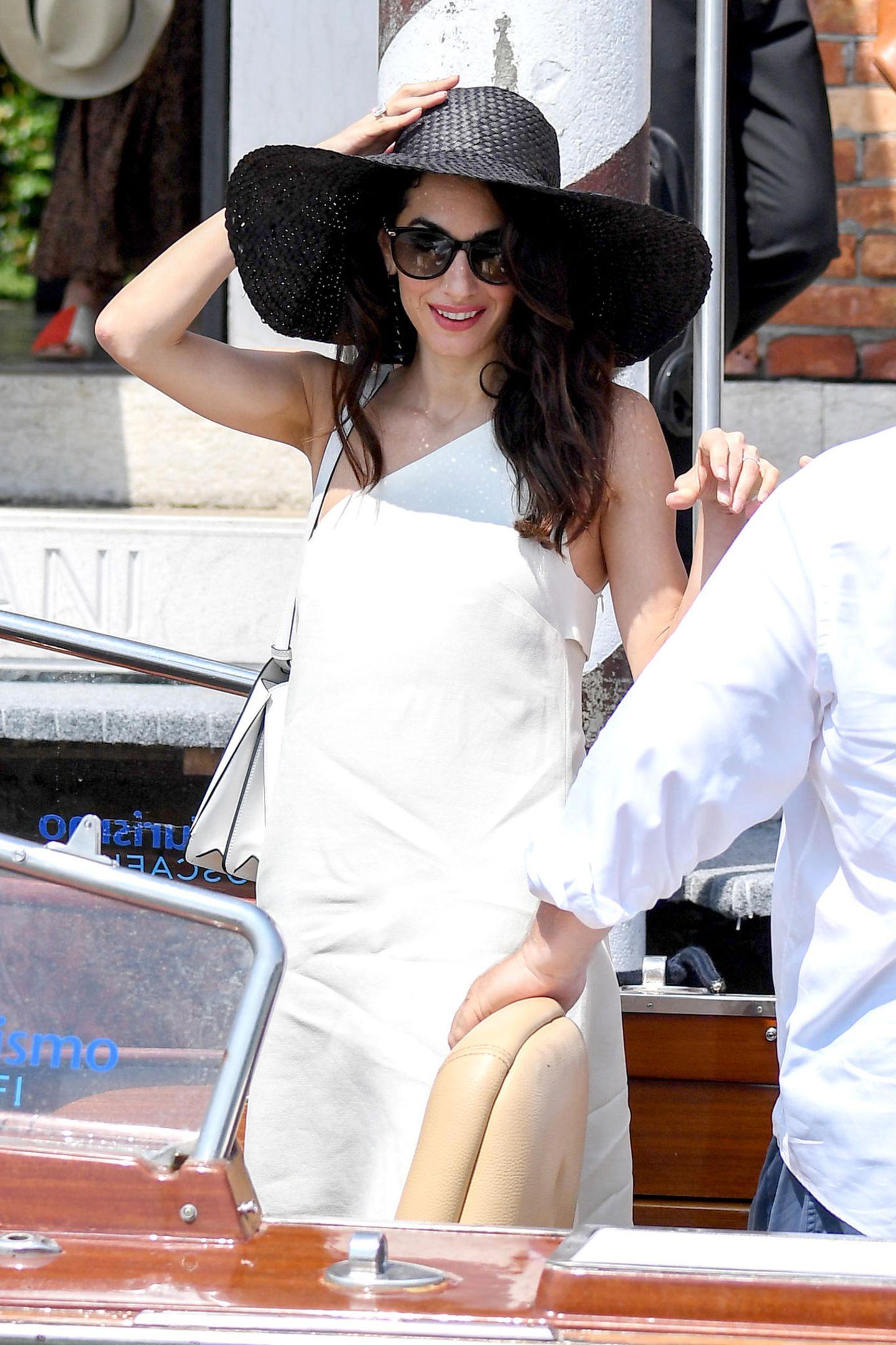 Das Kleid von Amal ist total schlicht geschnitten, wirkt durch den One-Shoulder-Cut jedoch äußerst raffiniert. Der Hut und die XXL-Sonnenbrille versprühen dazu den nötigen Glamour.