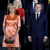 Beim G20-Gipfel in Osaka posieren Brigitte Macron und Emmanuel Macron für ein Gruppenfoto. Frankreichs First Lady dürfte auf diesem Foto jedem in ihrem Outfit ins Auge fallen. Brigitte trägt ein seidiges Minikleid in Orangetönen, das mit schwarzen Reißverschlüssen im Schulterbereich versehen ist. Dazu kombiniert sie eine schwarze Clutch.