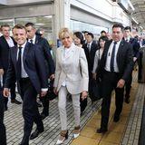 Einen Tag zuvor zeigt sich Brigitte Macron in einem ganz anderen Look. Sie trägt einen hellen, gestreiften Hosenanzug in Kombination mit schwarz-weißen Pumps. Besonders sympathisch: Sie fährt U-Bahn.