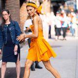 Auf den Straßen New Yorks ist Sängerin und Schauspielerin Zendaya in diesem Look ein echter Hingucker. Zendaya trägt ein raffiniertes Minikleid in Orangetönen in Kombination mit einem Haarband in derselben Farbe.