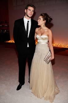 """Im März 2010 läuft ihr gemeinsamer Film """"Mit dir an meiner Seite"""" im Kino an. Zur gleichen Zeit zeigen sich Liam Hemsworth und Miley Cyrus - sehr passend - erstmals Seite an Seite auf einem roten Teppich. Sie wählt für diese Premiere einen glänzenden Tülltraum in Creme, der als Oberteil eine Satin-Corsage hat und ab der Taille herab mit Glitzersteinchen besetzt ist."""