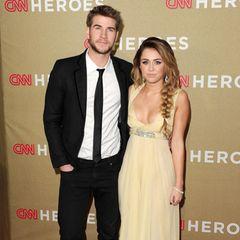 """Im Dezember 2011 hält Miley Cyrus noch immer an ihrem mädchenhaften Image fest. Dazu gehören auch romantische Kleider und Fischgrätenzöpfe. Liam Hemsworth hingegen pfeift gerne Mal auf die """"feine Etikette"""". Statt in klassische Anzugschuhe zu schlüpfen, geht er lieber in bequemen Schnürboots über den roten Teppich."""