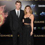 """Was für ein hübsches Paar! Bei der """"Hunger Games""""-Premiere begleitet Miley Cyrus ihren Liam in das Nokia Theatre in L.A. und hält sich dabei dezent zurück. Im schwarzen Zweiteiler aus Maxirock und Crop-Top ist sie eine zurückhaltende Schönheit, sodass er volle Aufmerksamkeit bei """"seiner"""" Premiere erhält."""