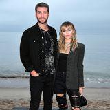 Etwas rockig, etwas schick. Vor allem aber eins: ganz schön lässig. Bei der Schau von Saint Laurent in Malibu geben Liam Hemsworth und Miley Cyrus ein cooles Glam-Rock-Pärchen ab.