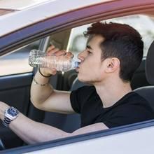 Mann trinkt im Auto aus Plastikflasche Wasser