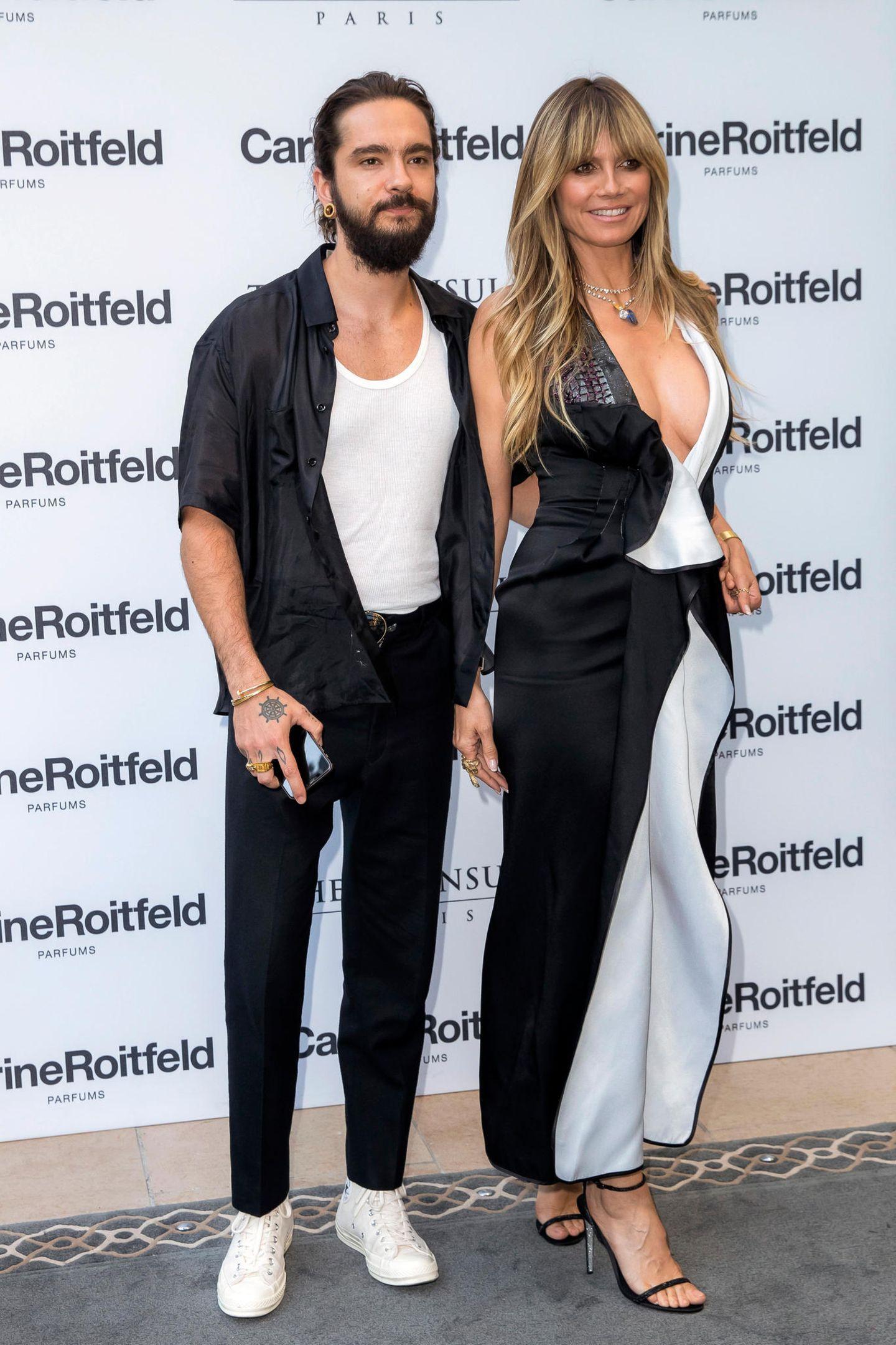 Denn auch Tom setzt auf einen schwarz-weißen Look. Er kombiniert eine schwarze Hose mit einem weißen Tanktop und einem schwarzen Hemd. Dazu trägt er weiße Sneaker.