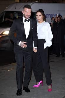 Das nennen wir mal einen perfekten Partnerlook: Während Göttergatte David Beckham einen klassischen Smoking trägt, wählt seine designende Ehefrau ein ebenfalls monochromes Outfit in Schwarz und Weiß, das lediglich durch knallpinke Pumps gebrochen wird.