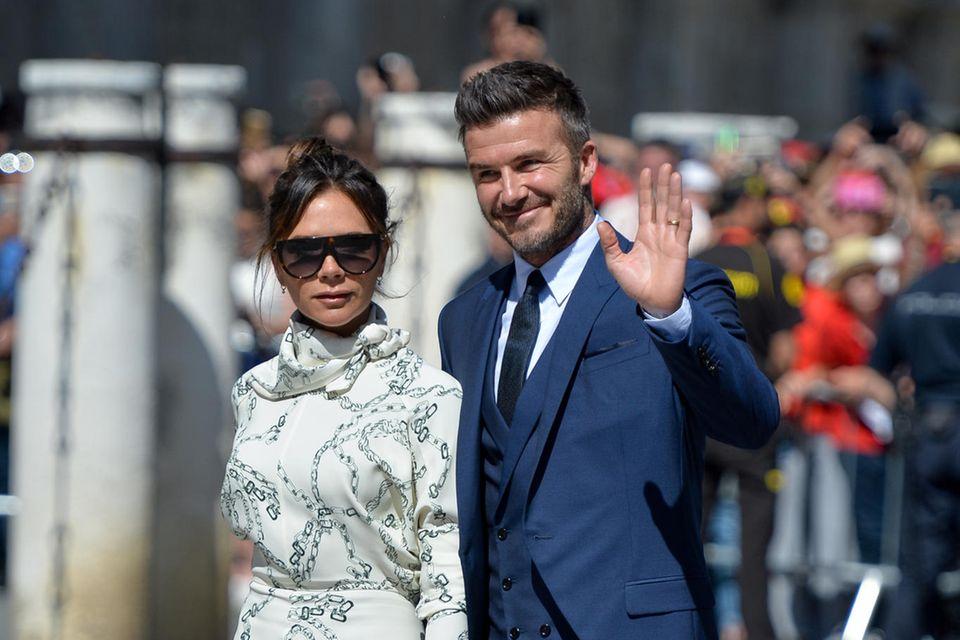 Bei der Hochzeit von Sergio Ramos und Pilar Rubio begeistern David Beckham und Ehefrau Victoria Beckham mit ihrer englischen Eleganz. Schmale Silhouetten und zurückhaltende Farben überlassen das Scheinwerferlicht gekonnt dem Brautpaar.