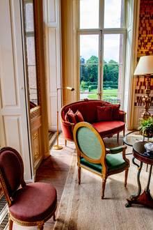 Den Blick auf den kunstvoll gestalteten Garten kann man in gemütlichen antiken Sitzmöbeln beim Tee genießen.