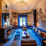 Die Bibliothek mit großem Kamin und gemütlichem, langem Samtsofa ist in beruhigenden Blau gehalten.