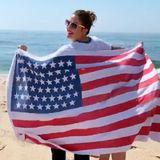 Drew Barrymore macht vor Freudeeinen kleinen Flaggentanz am Strand.