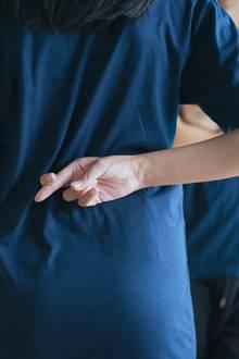 Frau kreuzt die Fingern hinter dem Rücken