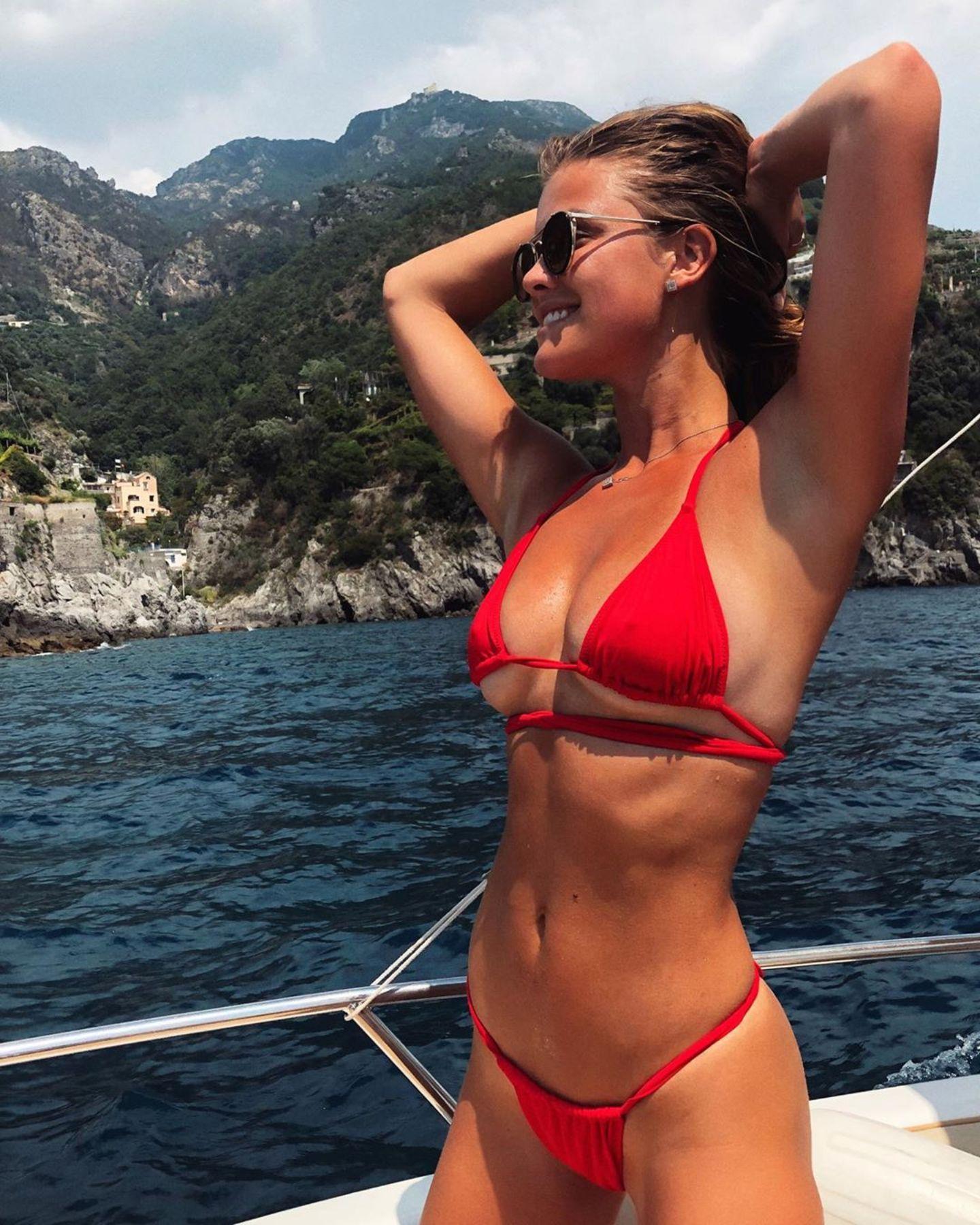 """In einem knallroten Bikini posiert Nina Agdal für ein Urlaubsfoto. Eine ziemlich knappe Kiste, denn sie setzt sowohl ihren """"Underboob"""" als auch ihren """"Sideboob"""" in Szene. Ein Schnappschuss, für den Ninajede Menge Likes kassiert. Wo genau das Bild entstanden ist, verrät das ehemalige Victoria's-Secret-Model nicht. Lediglich die Flagge Italiens grenzt das Rätselraten um ihre Destination ein."""