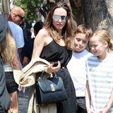 Zum Lunch mit ihren Zwillingen Knox und Vivienne trägt Angelina Jolie ein bequemes Outfit: Zu einer schwarzen, luftigen Leinenhose kombiniert sie ein schlichtes schwarzes Top mit Spaghettiträgern und setzt mit ihren gelben Sandalen und rot lackierten Fingernägeln farbliche Akzente. Doch ein modisches Detail wertet ihren Look besonders auf ...