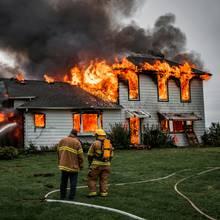 Feuerwehrmänner bekämpfen einen Wohnhausbrand