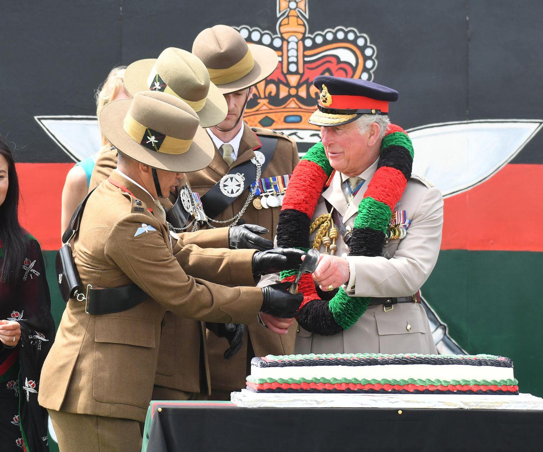 """9. Juli 2019  Prinz Charles bekommt bei seinem Besuch des 1st Battalion """"The Royal Gurkha Rifles"""" ein traditionelles Khukuri-Messer überreicht, um damit die Torte zur Feier anlässlich des 25. Gründungsjubiläum anzuschneiden."""