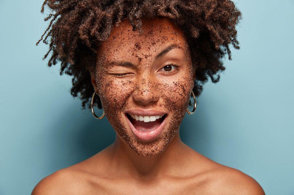 Peeling selber machen, zwinkernde Frau mit Peeling im Gesicht