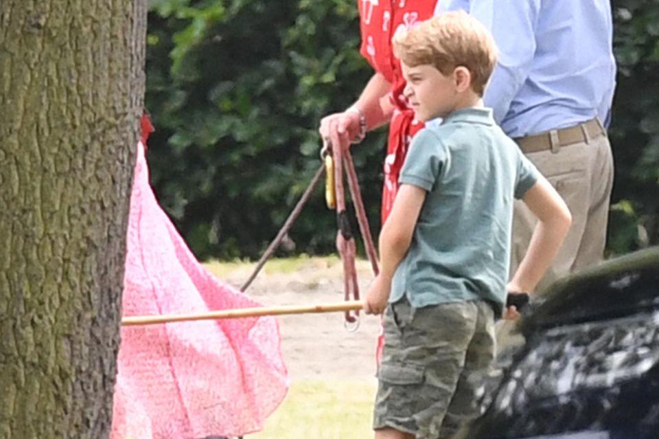 Prinz George lässt es sich nicht nehmen, seinen Vater beim Polo anzufeuern. Mit seinem T-Shirt und der Cargohose ist er für das Sportevent bestens gekleidet.