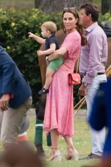 In einem pinken Blumenkleid besucht Herzogin Catherine ein Charity-Polo-Spiel im britischen Wokingham, an dem ihr Mann William und auch Prinz Harry teilnehmen. Auf dem Arm hält sie den kleinen Prinz Louis und dreht sich skeptisch zu den Fotografen um.