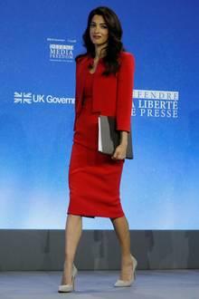 """What a Woman! Amal Clooney kann nicht nur Red Carpet, auch in ihrem Job als hochangesehene Menschenrechtsanwältin beweist sie Stilgespür. Das rote Ensemble stammt aus der Zac Posen Resort-Kollektion 2019, ist aus feinstem Crepe-Stoff gefertigt und trägt die schöne Farbbezeichnung """"Cranberry""""."""