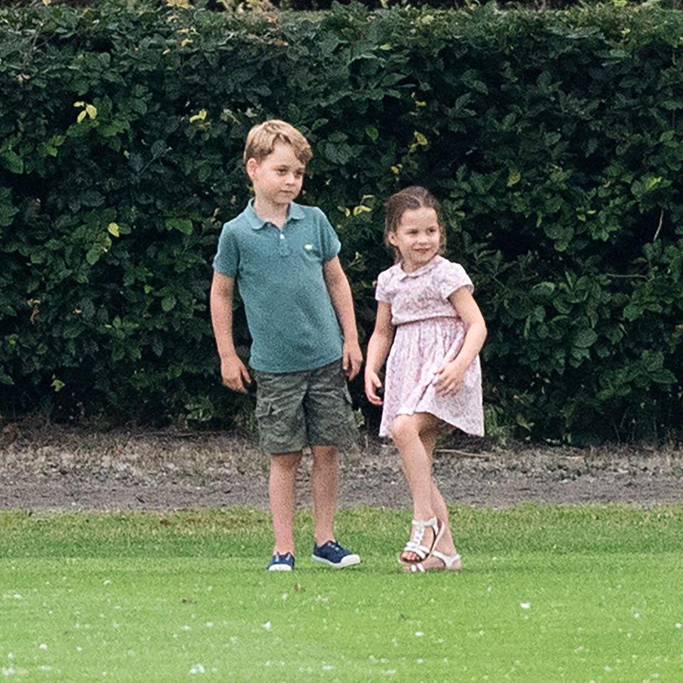 """Schnäppchen-Prinz George: Beim Familienausflug zum Charity Polo Turnier ist Prinz George in einem echten Schnäppchen-Look unterwegs. Der kleine Prinz trägt ein Poloshirt von H&M (ca. 7 Euro) und eine Shorts von Gap (ca. 27 Euro)in Kombination mit den """"Hampton Canvas Plum Shoes"""" von Trotters (ca. 30 Euro)."""