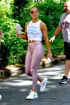 """Auf dem Weg ins Gym durchquert Jennifer Lopez den Central Park. Hier können wir einen Blick auf ihren tollen Look erhaschen, der eine wirklich perfekte Kombination ist. Auf ihrem Tanktop von """"Victoria's Secret"""" schillert ein Logo-Muster, dasgenau zu ihrer irisierenden Leggings passt. Diese wiederum nimmt den Roséton ihrer Sneaker wieder auf, die gleichzeitig auch zum Oberteil passen. Das Beste an ihrem Style bleibt jedoch ihre """"Wasserflasche"""", ein großer, sahniger Iced Macchiato, der komplett mit Kristallen besetzt ist und ihre unglaublichen Muskeln."""