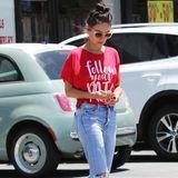 """Mila Kunis rät mit ihrem Shirt allen: """"Follow your path"""". Also """"Folgt eurem Weg"""". Zu dem Statement-Oberteil wählt sie eine Mom-Jeans mit zerrissenen Knien."""