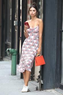 Warum zieht Emily Ratajkowski bloß so eine Schnute? An ihrem Look kann es ja wohl kaum liegen! Ihr hübsches Kleid mit leichtem Wasserfallausschnitt und Spaghettiträgern kombiniert sie zu klassischen Sneakern von Adidas und einer orangeroten Boxy-Bag, die eigentlich gute Sommerlaune versprüht.