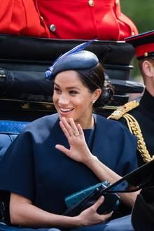 """8. Juni 2019  Die Queen hat zu ihrer traditionellen Geburtstagsparade """"Trooping the Colour"""" geladen. Für Herzogin Meghan ist es ihr erster öffentlicher Auftritt nach der Geburt von Baby Archie. Sie winkt überglücklich und freut sich über die Fahrt in der Kutsche, in der ihr Herzogin Catherine gegenüber sitzt."""