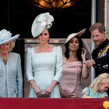 """9. Juni 2018  Meghan hat ihren ersten Auftritt als Herzogin. Nicht einmal einen Monat ist ihre Hochzeit mit Prinz Harry vorbei. Nun steht sie auf dem Balkon des Buckingham Palace und verfolgt die """"Trooping the Colour""""-Parade. Die Regeln und Rangordnungen sehen es jedoch vor, dass sie erst einmal nur in der zweiten Reihe stehen darf. Herzogin Catherine darf hingegen am Geländer stehen."""
