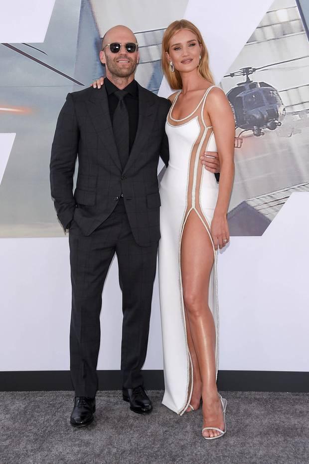 """Bei der Weltpremiere von """"Fast & Furious Presents: Hobbs and Shaw"""" zeigt Rosie Huntington-Whiteley endlos viel Bein. Der Schlitz ihres Kleides wird optisch durch einen transparenten Stoff verlängert, der sich ganz bis zum Dekolleté zieht und von einer Glitzerbahn umgeben ist. Ihr Liebster, Jason Statham, steht hingegen komplett im Kontrast zu ihr. Er zeigt sich hochgeschlossen und komplett in Schwarz."""