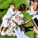 Die Gratulanten haben sich alle hinter einer Absperrung versammelt. Prinzessin Victoria gesellt sich zu ihnen und nimmt - auch von den Kleinsten - Glückwünsche und Geschenke entgegen. Prinz Oscar gibt ihr dabei Rückendeckung.