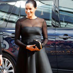 Herzogin Meghan von Kopf bis Fuß in schwarz gekleidet. Ihr Kleid ist von Jason Wu, ihre Clutch von Gucci.