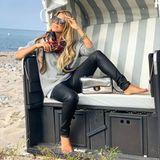 """Auf den ersten Blick trägt Sylvie Meis ein lässiges Strandoutfit mit Sweatshirt, Tuch, Sonnenbrille und Lederleggings. Doch siehe da: Auch die edle Chanel-Tasche aus PVC sowie luxuriöser Schmuck, u.a. der """"Love""""-Armreif von Cartier, dürfen nicht fehlen."""