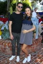 Stolz hält Miranda Kerr die Hand auf ihren wachsenden Babybauch. In einem luftigen, blauen Sommerkleid und mit knallroten Lippen besucht die Schwangereein Event in Beverly Hills. Lässig hat sie eine hellblaue Jeansjacke über ihre Schultern geschwungen und auch an den Füßen mag es die 36-Jährige an diesem Tag bequem: So trägt sie schlichte, weiße Sneaker – ebenso, wie ihr Mann, Evan Spiegel, der sie zu dem Event begleitet. Wer da bei wem im Kleiderschrank gestöbert und sich als erstes in die schicken Streetstyle-Schuhe verliebt hat, bleibt jedoch das süße Geheimnis von Miranda und Evan.