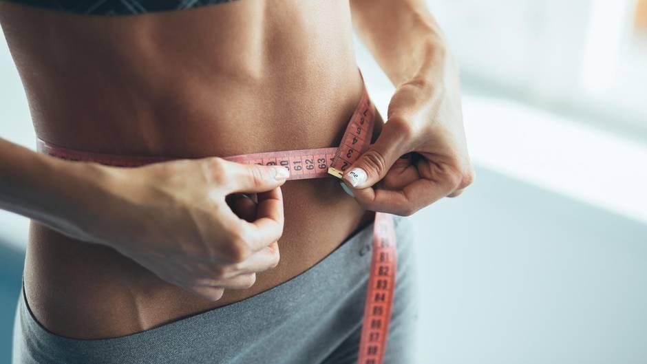 Frau checkt mit einem Maßband ihren Taillenumfang