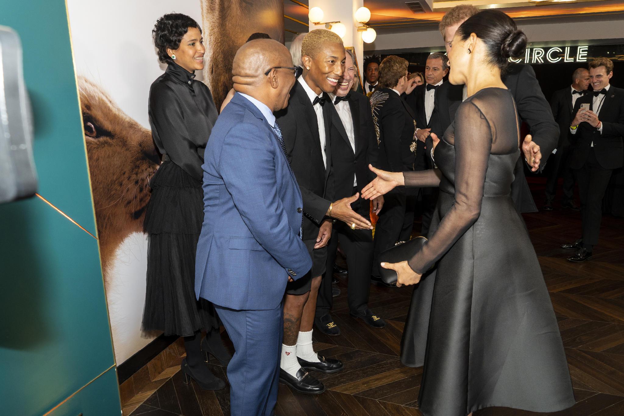 """Musiker Pharrell Williams begrüßt Herzogin Meghan bei der Premiere von """"The Lion King"""" in London und macht ihr ein Kompliment über ihre Beziehung zu Prinz Harry. Dabei macht die frisch gebackene Mutter eine überraschende Aussage"""