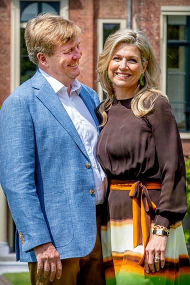 """Kein Wunder, dass König Willem-Alexander seine Ehefrau so überglücklich anstrahlt: Königin Máxima sieht beim diesjährigen Sommershooting mal wieder umwerfend aus. DieMonarchin trägt anlässlich des offiziellen Fototermins ein Kleid des niederländischen Designers Jan Timinau. Das farbenfrohe Dress trägt den Namen """"Orange Desert"""" und kostet im Onlineshop des Labels 1490 Euro. Zu dem Sommerkleid kombiniert Máxima grüne Ohrringe der Marke Lott Gioielli. Die auffälligen Kreolen bestehen aus grünen Glasperlen."""