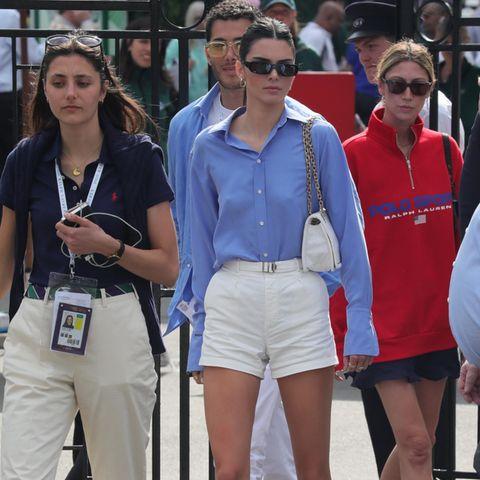"""Für einen Besuch in Wimbledon zeigt sich Kendall Jenner von ihrer sportlicheren Seite. In einem hellblauen Hemd, weißer Shorts und mit Prada-Tasche unter dem Arm macht sie eine tolle Figur. Und auch das junge Supermodel, das Kampagnengesicht von Adidas ist, weiß teure It-Pieces mit erschwinglicheren Teilen zu kombinieren: Sie trägt das Sneaker-Modell """"Continental"""" des deutschen Labels für unter 100 Euro."""