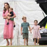 Als Herzogin Catherine mit den drei Kindern ein Charity-Polo-Match ihres Mannes besucht, ist die Welt verzückt! Die Fotos vom Ausflug, bei dem sogar auch Herzogin Meghan und ihr Sohn Archie dabei sind, zeigen die Royals als (fast) ganz normale Familie. Prinzessin Charlotte (ganz rechts) trägt ein geblümtes Kleid mit Kragen, Prinz George erscheint in grünem Poloshirt und Cargo-Shorts.