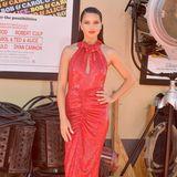 Adriana Lima setzt ihre Topfigur in einem glitzernden roten Kleid mit Raffung in Szene.