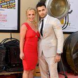 Britney Spears und ihr FreundSam Asghari erscheinen gemeinsam auf dem roten Teppich der Premiere. Wer glaubt, dass Britneys knallrotes Kleid an diesem Abend alle Blicke auf sich zieht, liegt falsch - viel mehr Aufsehen erregt der Ring an ihrer Hand, der für Verlobungsgerüchte sorgt.