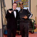 Die Pose sitzt: Quentin Tarantino und Snoop Dogg lächeln für die Kameras. Während der Star-Regisseur auf einen schwarzen Samt-Anzug setzt, erscheint der Rapper in einem sportlichen Zweiteiler und mit Sonnenbrille.