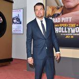 Leonardo DiCaprio erscheint in einem dunkelgrauen Anzug.