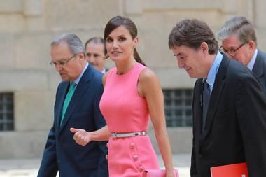 Königin Letizia zieht in einem pinken Kleid von Michael Kors alle Blicke auf sich. Auch die Accessoires - eine Clutch und die Pumps von Magrit - sind pink! Einzig der dünne Taillengürtel, der ihre schmale Taille betont ist silber.